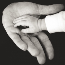 Baby hand on adult hand