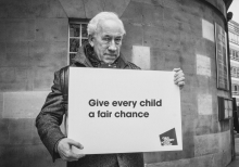 Actor Simon Callow holding board saying give every child a fair chance