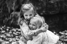Two smiling girls hugging each other